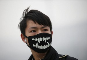 A man wearing a mask makes his way during a polluted day at Tiananmen Square in Beijing